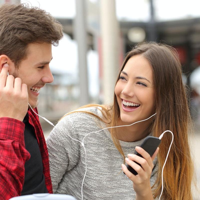 Forelsket par lytter til musik på telefonen