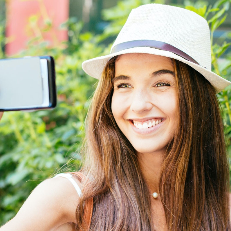 Pige tager selfie og bruger billedredigering.